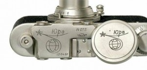 Zorki camera top cover and lens-cap with graphic depicting the orbit, and 'Yuri', in Cyrillic lettering. The date of the 'First Flight' also appears. The date of the 'First Flight' also appears.